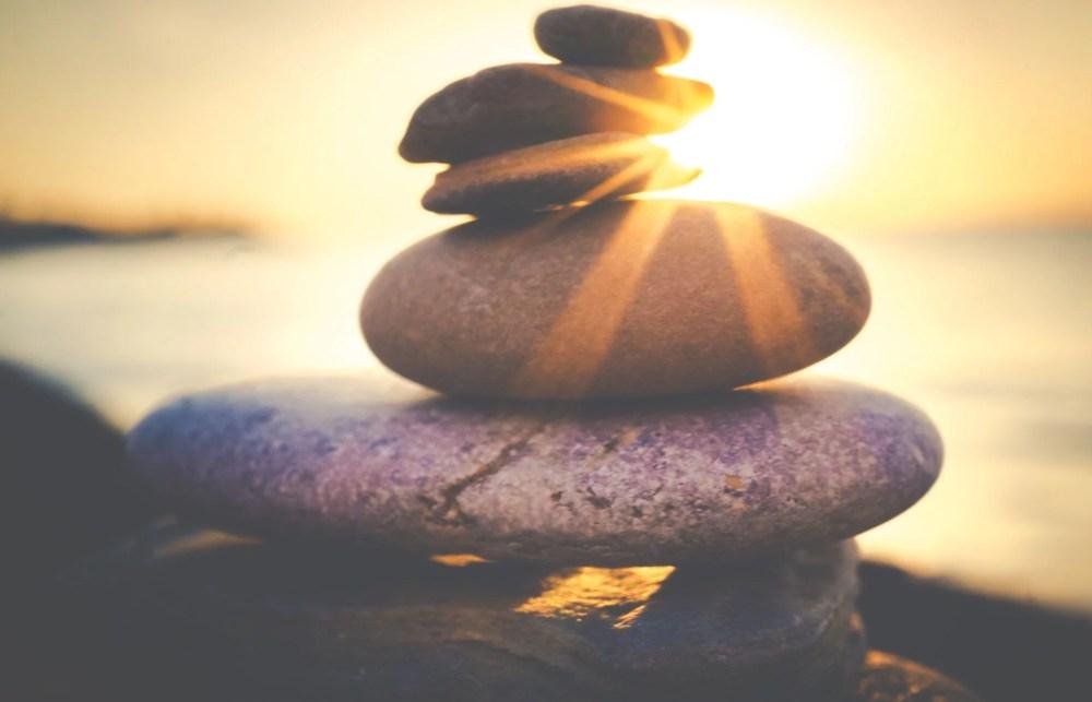 Sculture en pierre avec un coucher de soleil en fond. Cette image représente une pensée du jour dont la phrase est écrite par Hippocrate.