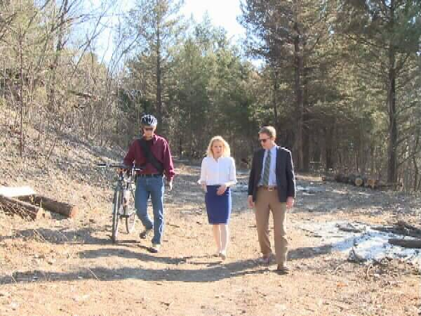 KOAM-TV reporter Stacey Lindsay walks with Lehigh Portland Trails volunteer Randy Rasa and Thrive Allen County Executive Director David Toland.