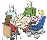 An einem Tisch sitzen zwei Männer, eine Frau und ein Rolstuhlfahrer. Sie sprechen miteinander.