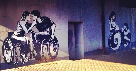 Zwei Schablonen-Graffitis auf einer Wand. Auf dem Bild links sieht man eine Frau und einen Mann, die kurz davor sind sich zu küssen. Beide sitzen im Rollstuhl. Daneben ist rechts ein Graffiti, bei dem eine schwangere Rollstuhlfahrerin ihren Bauch hält und ein Mann (Fußgänger) vor ihr kniet.
