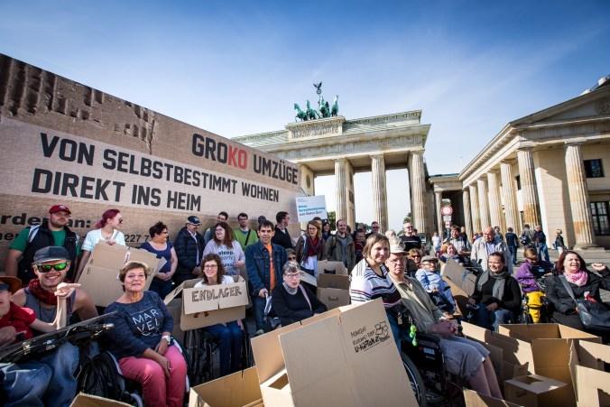 """Aktivistinnen und Aktivisten sitzen mit ihren Rollstühlen zwischen Umzugskartons vor dem Brandenburger Tor. Daneben steht auch ein Lastwagen mit der Überschrift """"Groko Umzüge. Von selbstbestimmt wohnen direkt ins Heim"""". Die Sonne scheint, der Himmel ist blau, die Menschen lächeln."""