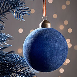 Blue Christmas bauble hanging on fir branch