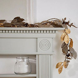 A gold leaf garland on top of a cream fire place mantle