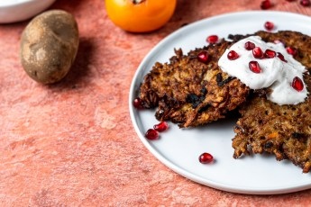 A plate of persimmon potato latkes with black pepper sour cream and pomegranate arils