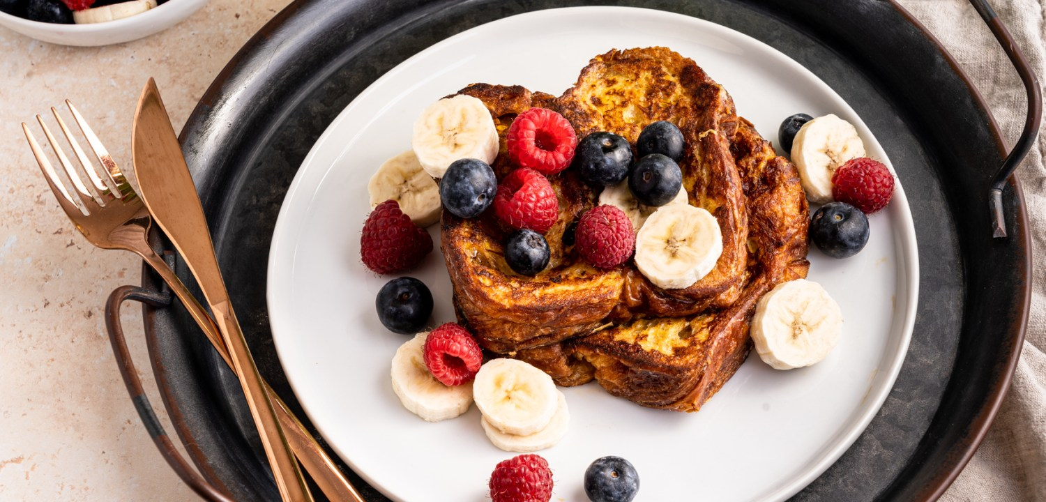 A header shot of cinnamon croissant French toast with banana slices, blueberries and raspberries.