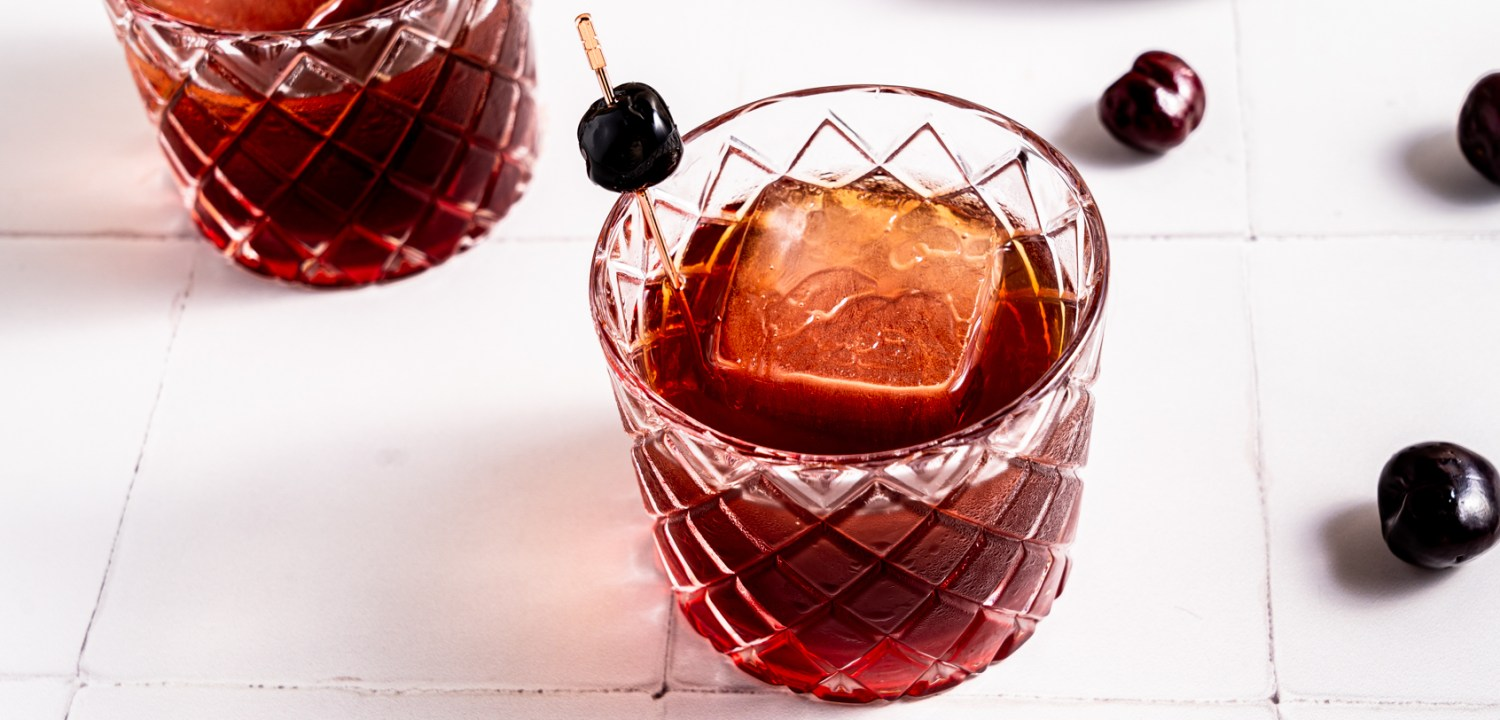 Header shot of a cherry Manhattan cocktail with a cocktail cherry.