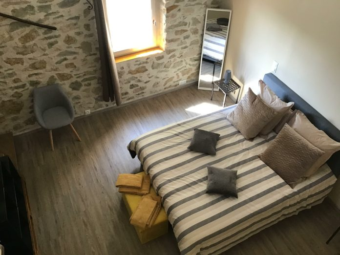 Location saisonnière gîte de Belley 3 étoiles à Montfort 04600 la chambre Muscade de 17 m2 en parquet miroir fauteuil table de chevet lampe avec lit 160 cm récent, en haut des escaliers incluant un espace détente avec mobilier se situe dans les Alpes-de-Haute-Provence 04.