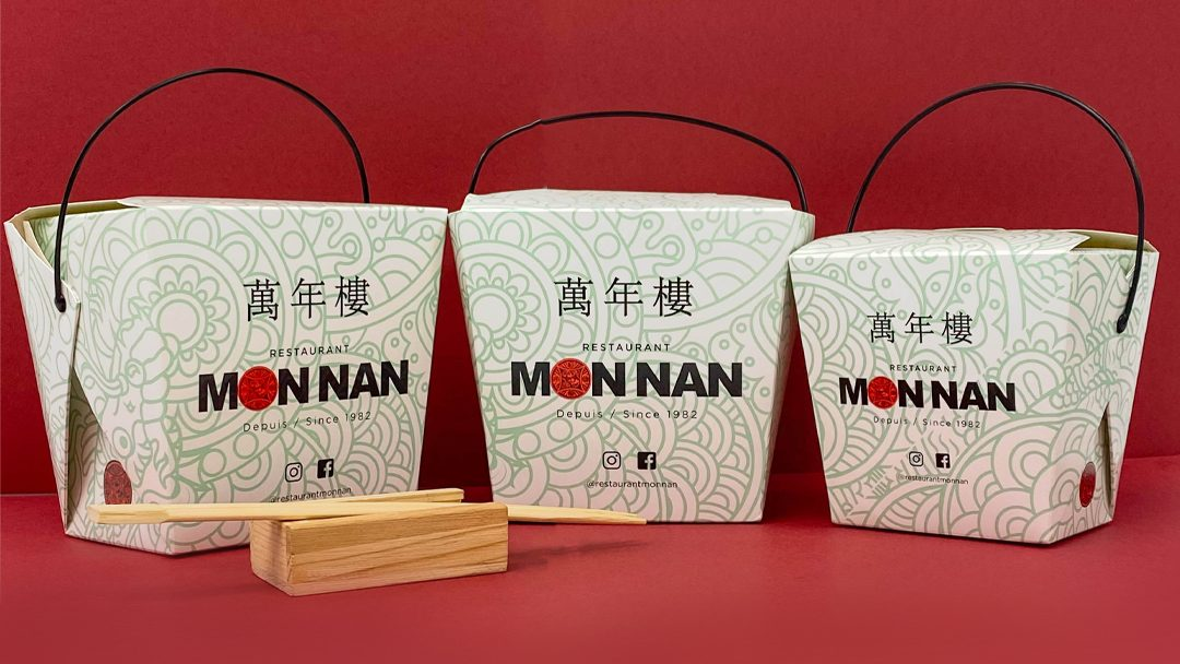 Three Chinese takeout boxes with light green print from the restaurant Monnan on a red background. A pair of chopsticks sits in front of the far left box.
