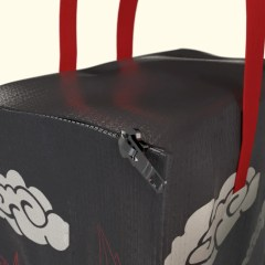 close up of a glossy laminated cooler bag with a flat top zipper closure and red PP non-woven handles.
