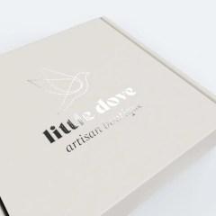 beige mailer box on white Kraft base with silver foil logo