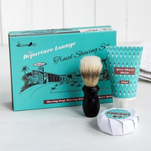 Teal cardboard packaging, a shaving brush, soap and aftershave bar.
