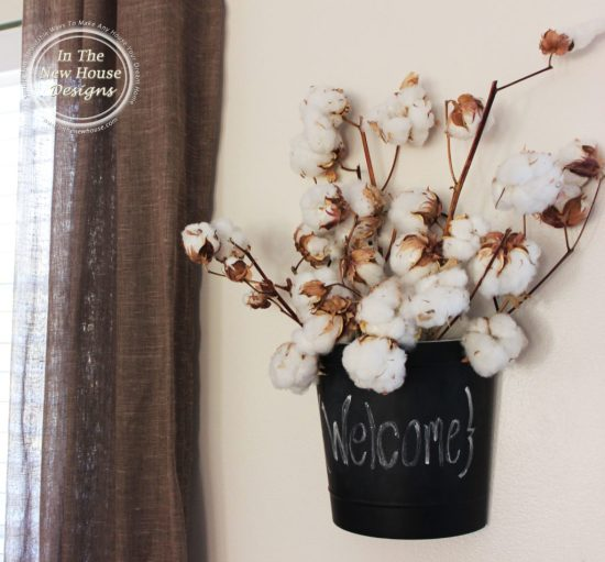 Cotton stems in a chalkboard half-bucket is great wall decor for an entry