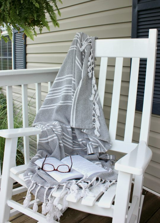 Front porch white rocking chair with cozy blanket and boston fern