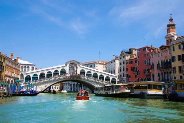 Venice Grand canal with gondolas and Rialto Bridge, Italy in summer bright day