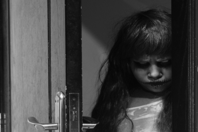 45107293 - a creepy little girl staring from behind the door
