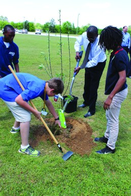 Principal McCray helps students plant trees