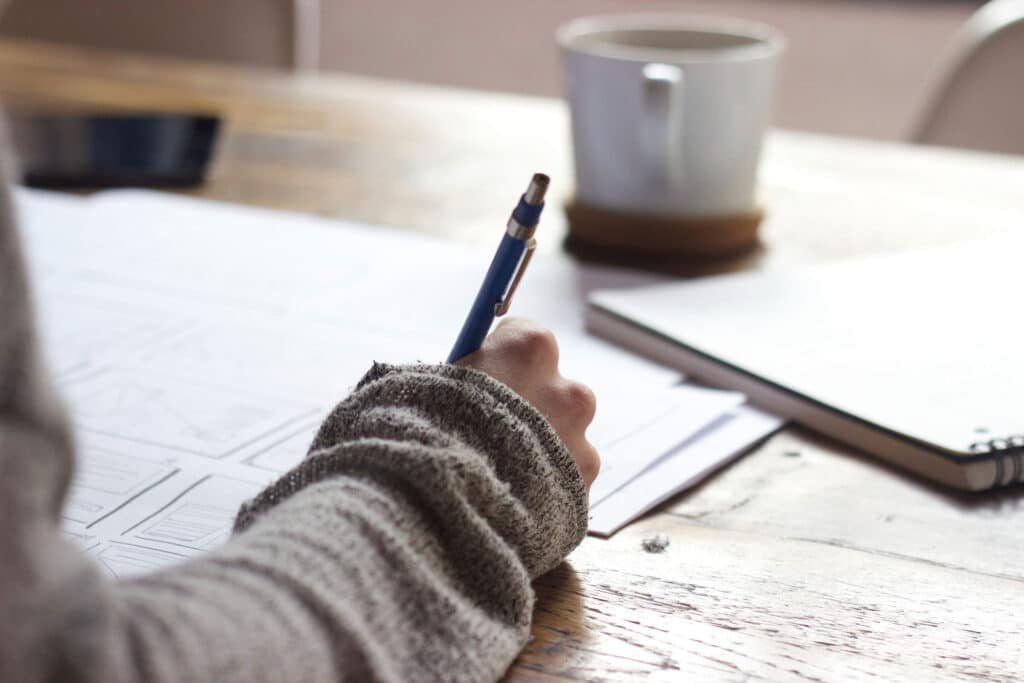 junge Frau arbeitet in Quarantäne an einem Mood-Board auf Papier an einem Schreibtisch aus Holz.