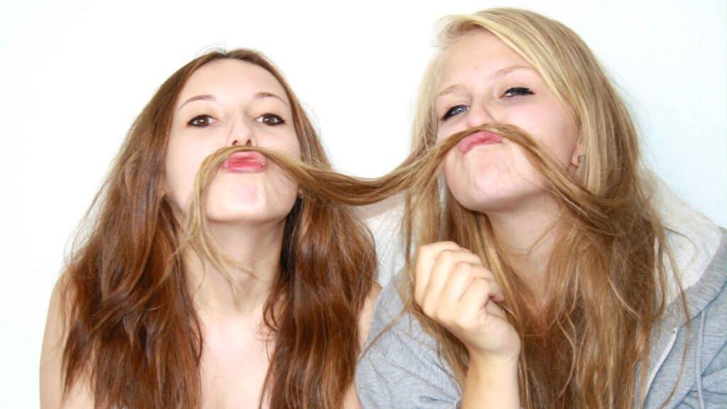 Zwei junge Frauen die die haare der einen geminsam als Schnurrbart verwenden. Aus dem Artikel: Warum wir aufhören sollten, für andere zu denken
