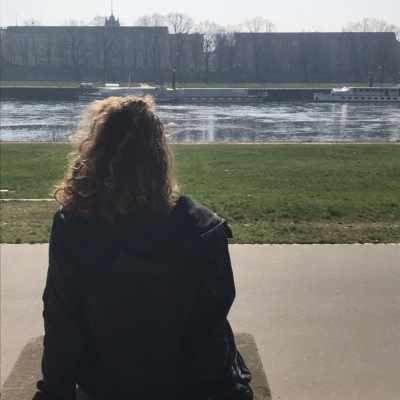 Junge frau mit mittellangen Locken sitzt mit dem Rücken zur Kamera mit Blick auf einen Kanal. Aus dem Artikel: Wir fordern, dass der Frauentag 365 Tage im Jahr ist.