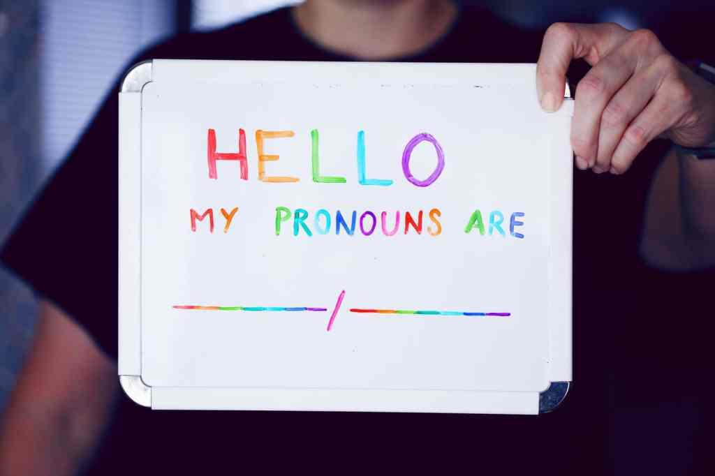 Person hält Schreibtafel mit Pronomenauswahl vor sich. Aus dem Artikel Gendern im Alltag – mitgemeint ist nicht mitgedacht