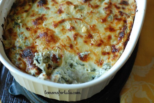 Missing scoop of delicious Tex Mex Spinach and Artichoke Dip in a white casserole dish.