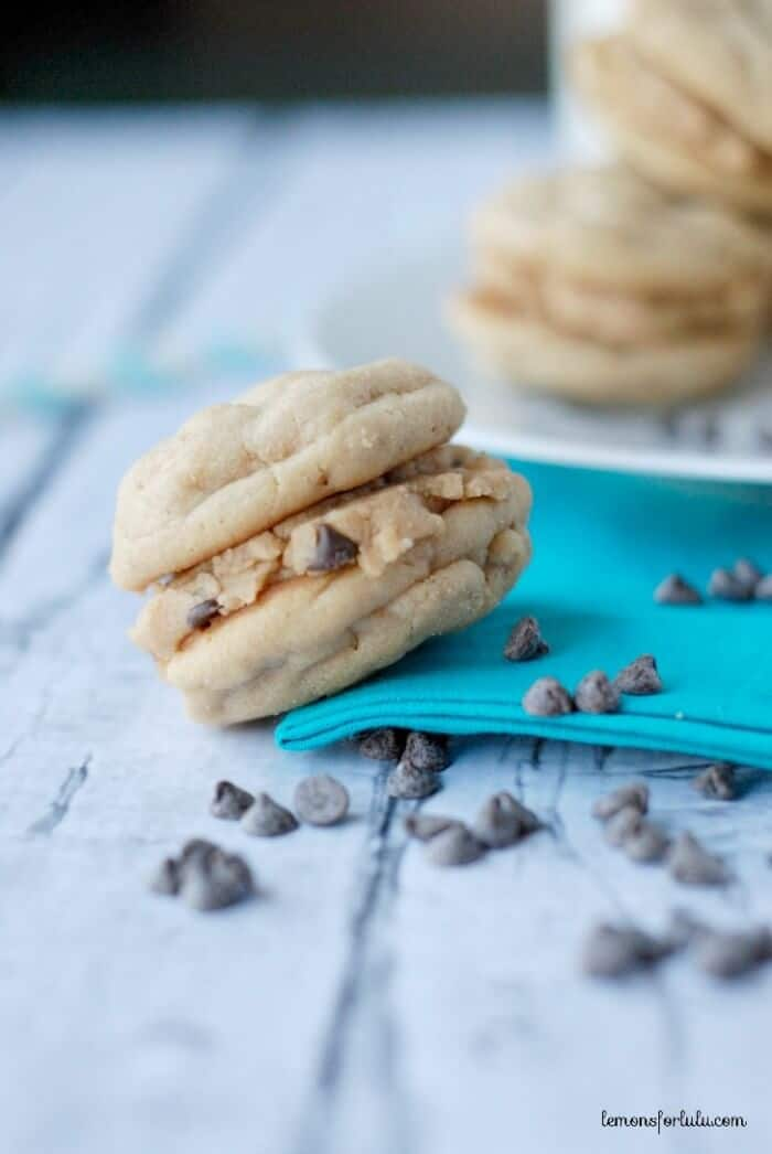 Oatmeal Peanut Butter Cookies with Peanut Butter Cookie Dough Filling on a blue cloth surrounded by chocolate chips on a wooden table.