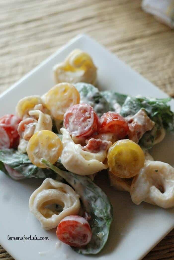 BLT tortellini salad comes together so easily! It's made with a simple Greek yogurt dressing and has lots of fresh tomatoes! www.lemonsforlulu.com #WalmartProduce