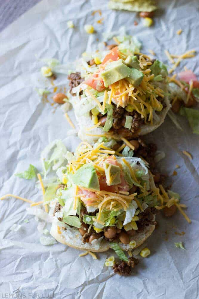 Two taco sloppy joes on parchment paper topped with tomatoes, cheese and lettuce.