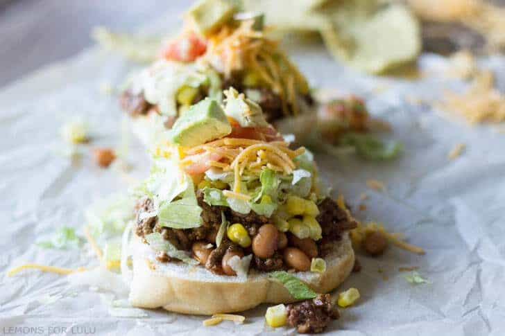 Delicious sloppy joes turned into tacos on parchment paper and topped with sweet corn, lettuce, cheese and tomatoes.