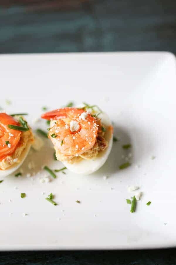 These Buffalo shrimp deviled eggs will be a hit wherever they go! The spicy shrimp are tamed by the tang blue cheese filling. Time to rethink the way you do deviled eggs! #OhioEggRoll