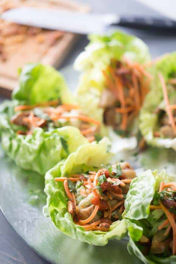These chicken lettuce wraps are such an easy recipe to make! Soy and ginger glazed chicken is surrounded by bibb lettuce and topped with chopped cucumber, shredded carrots and spicy Srirach almonds! lemonsforlulu.com