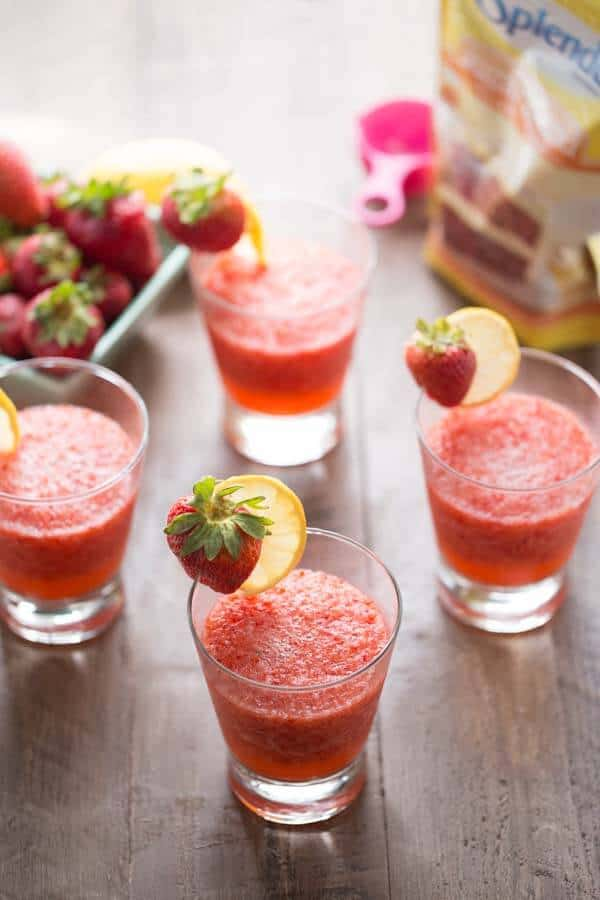Four simple strawberry rickey mocktails with refreshing strawberries next to a package of Splenda on a wooden table.