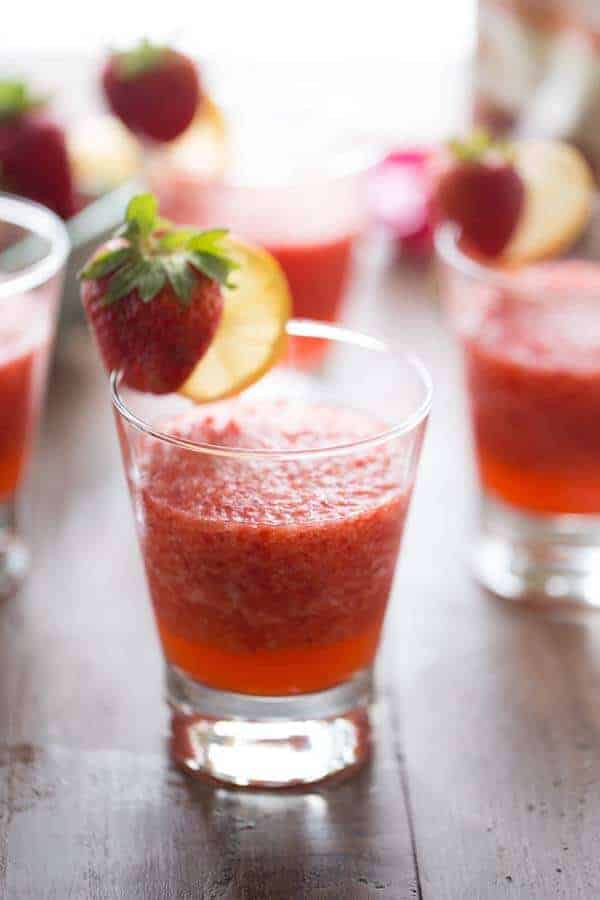 Refreshing Strawberry Rickey recipe in a glass drinking cup garnished with fresh strawberries and sliced lemon.