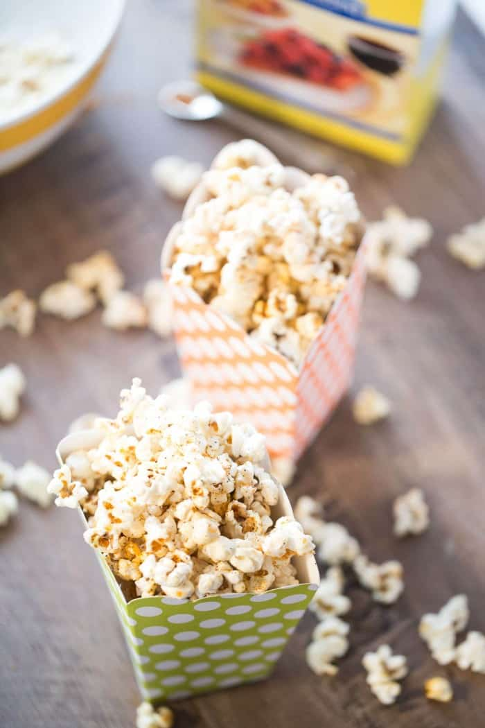 A smoky and sweet kettle corn in two green and orange popcorn containers on a wooden table.