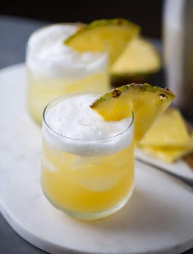 Pineapple Bourbon Punch - Bourbon, sweet pineapple juice, and hazelnut liqueur are shaken together for a tropical tasting drink.