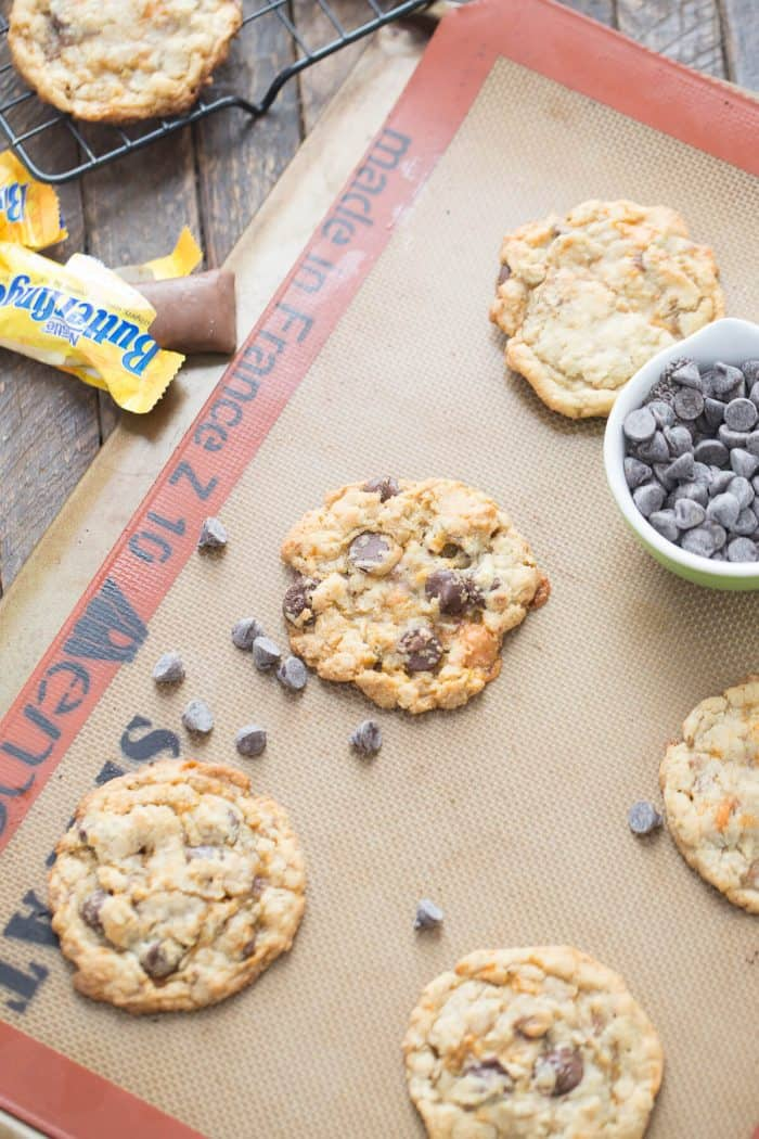 Four simple Butterfinger cookies surrounded by chocolae chips and an unwrapped Butterfinger.