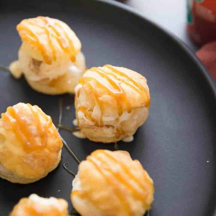 Five profiterole treats drizzled with caramel on a black serving plate.