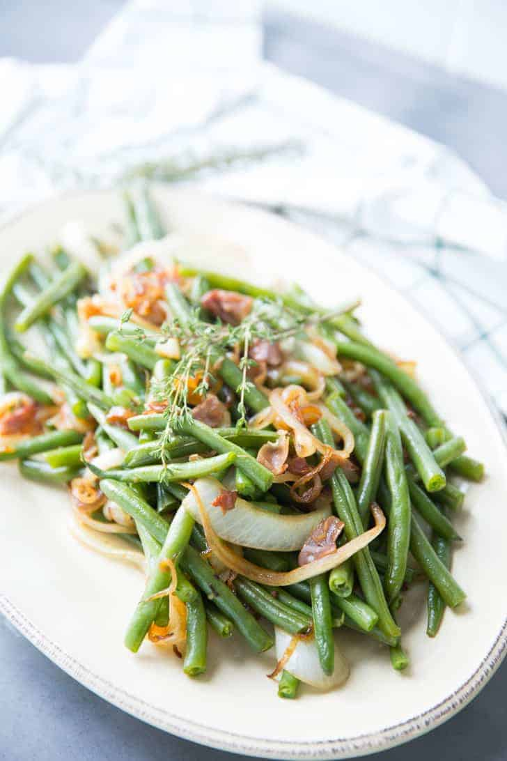 Delicious Green Beans recipe with balsamic dressing and caramelized onions on a white serving platter.