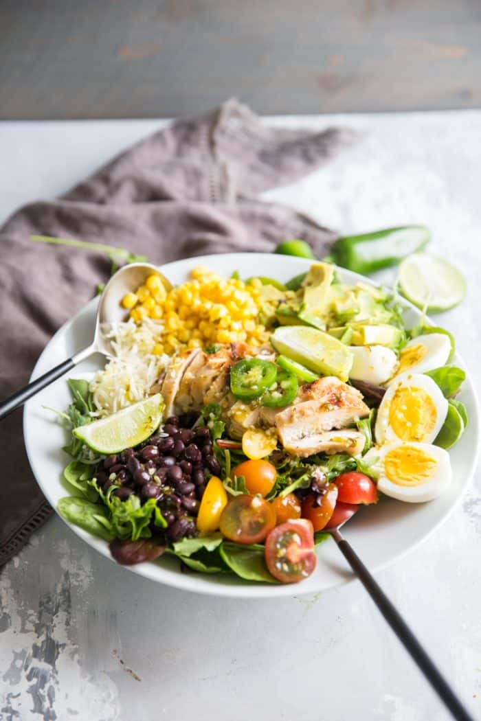 cobb salad with serving spoons