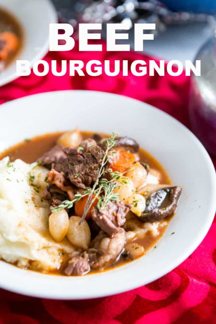 A bowl of food on a plate, with Beef and Beef bourguignon