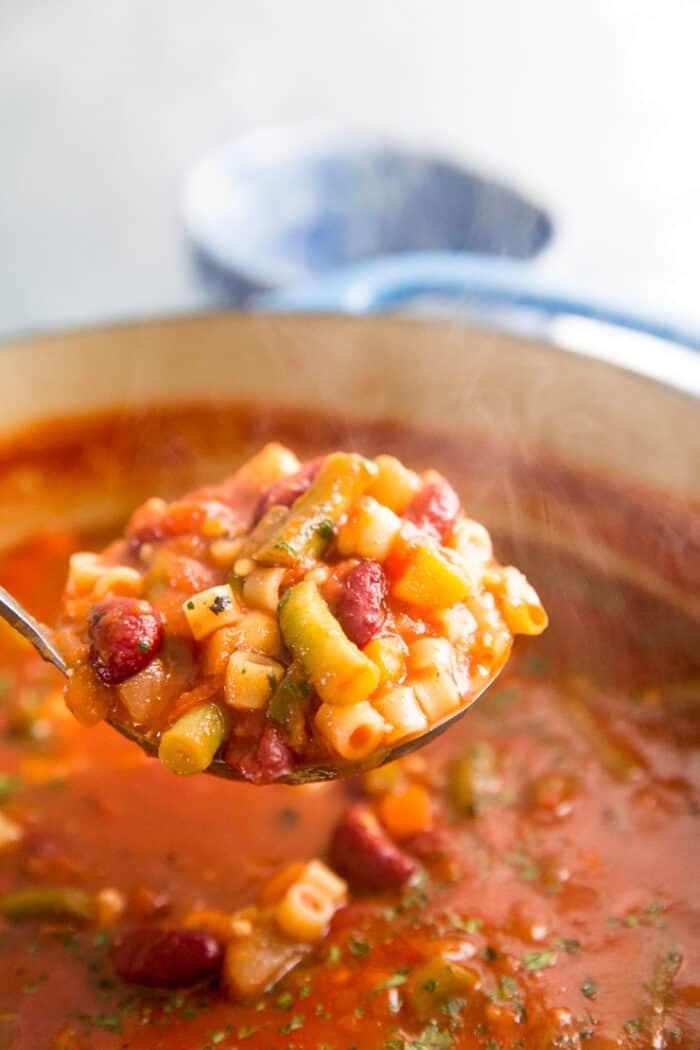 Minestrone soup ladle lifting soup