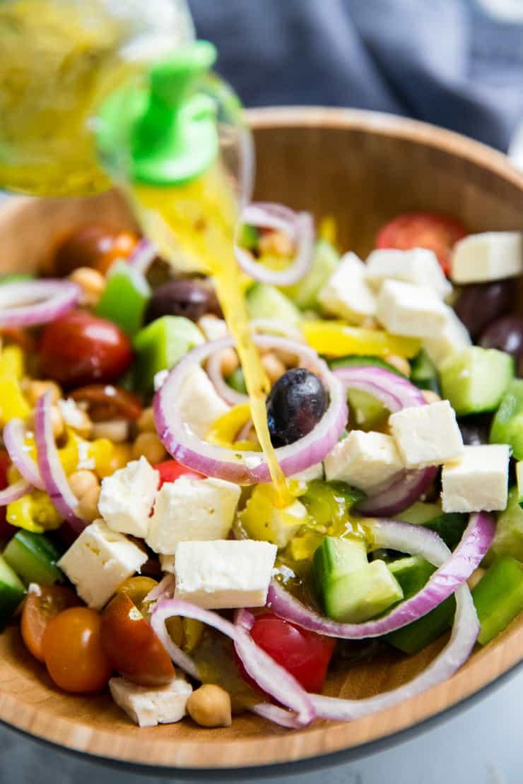 salad dressing poured over Greek salad