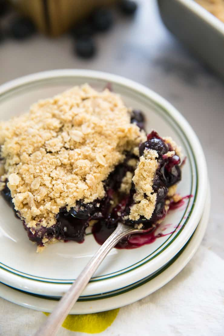 one slice of blueberry oatmeal bars with a fork taking a bite