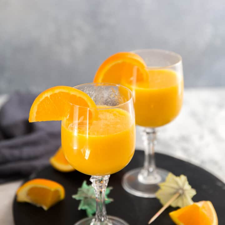 mango mimosa drink on black tray
