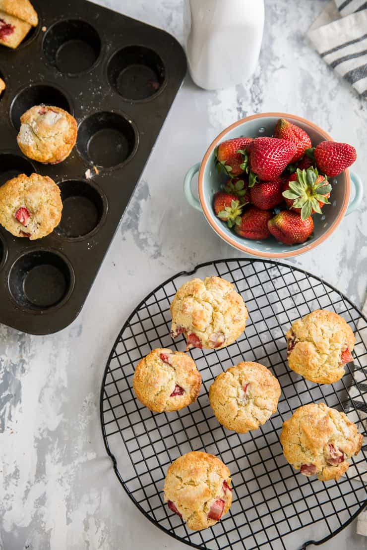 strawberry muffins on a cooling rack with some resting in the muffin tin next to it