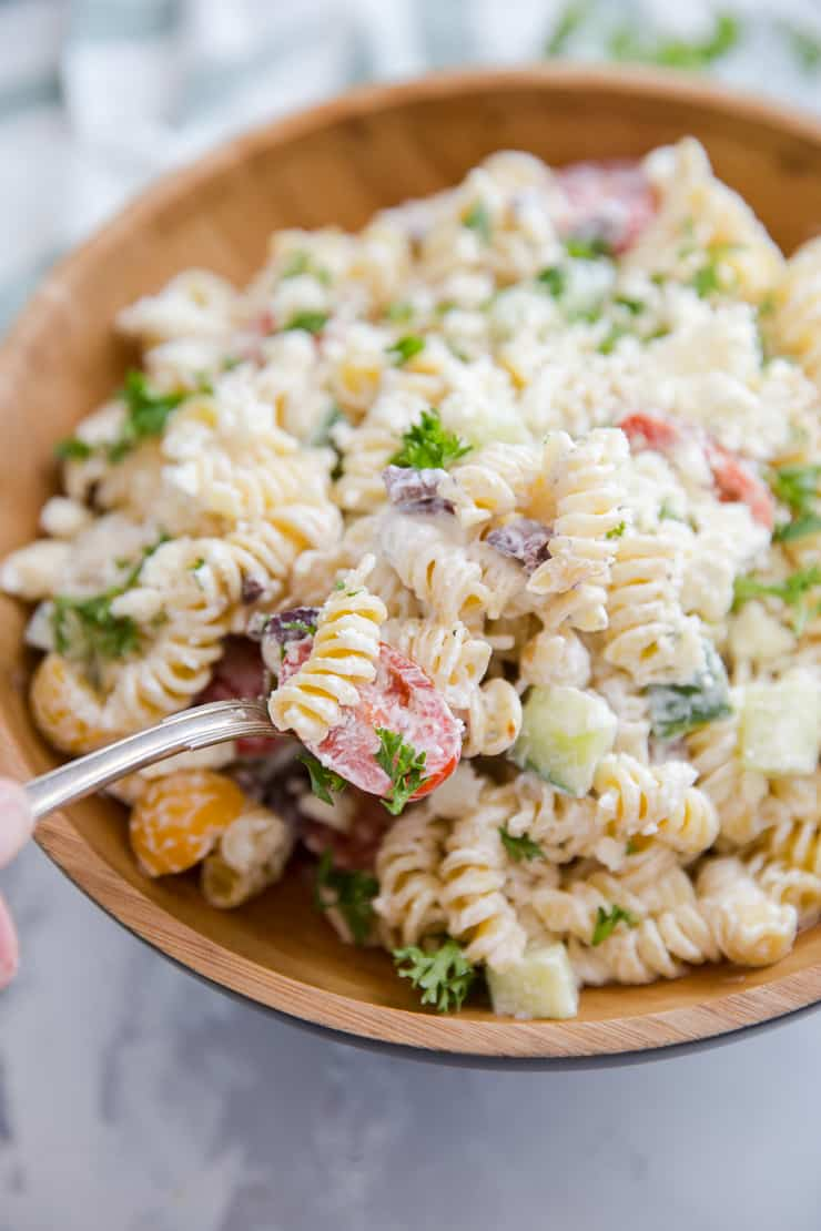 Greek pasta salad with a spoon serving it up