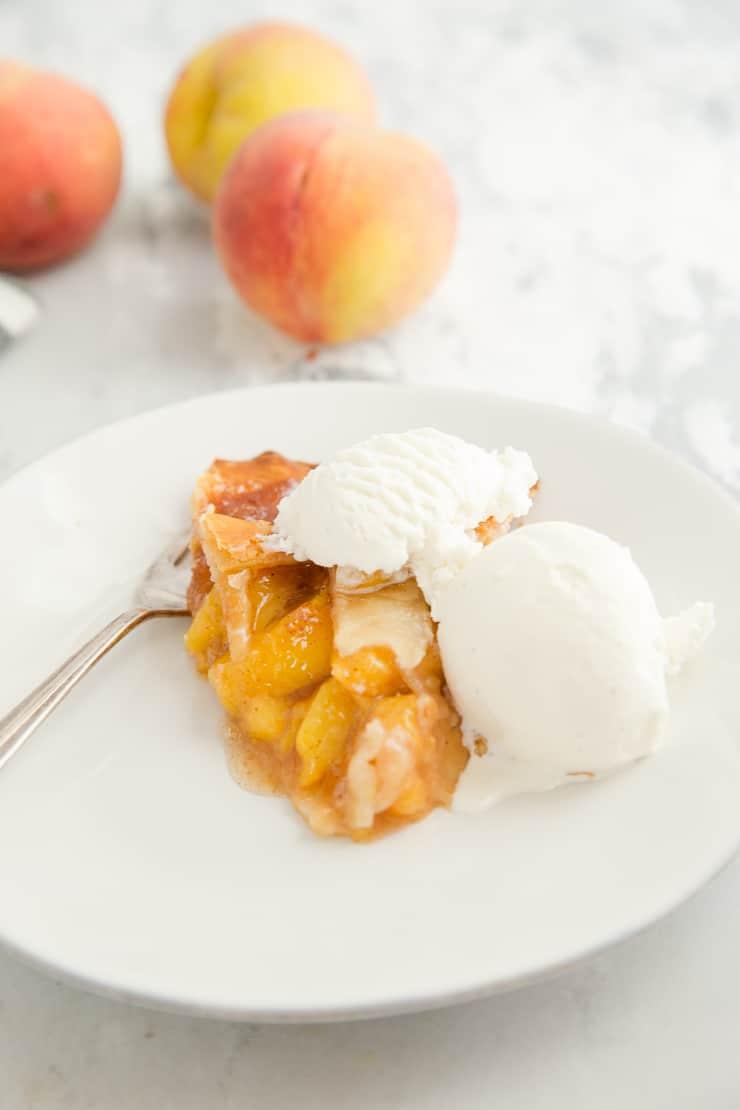 Piece of peach pie on a white plate