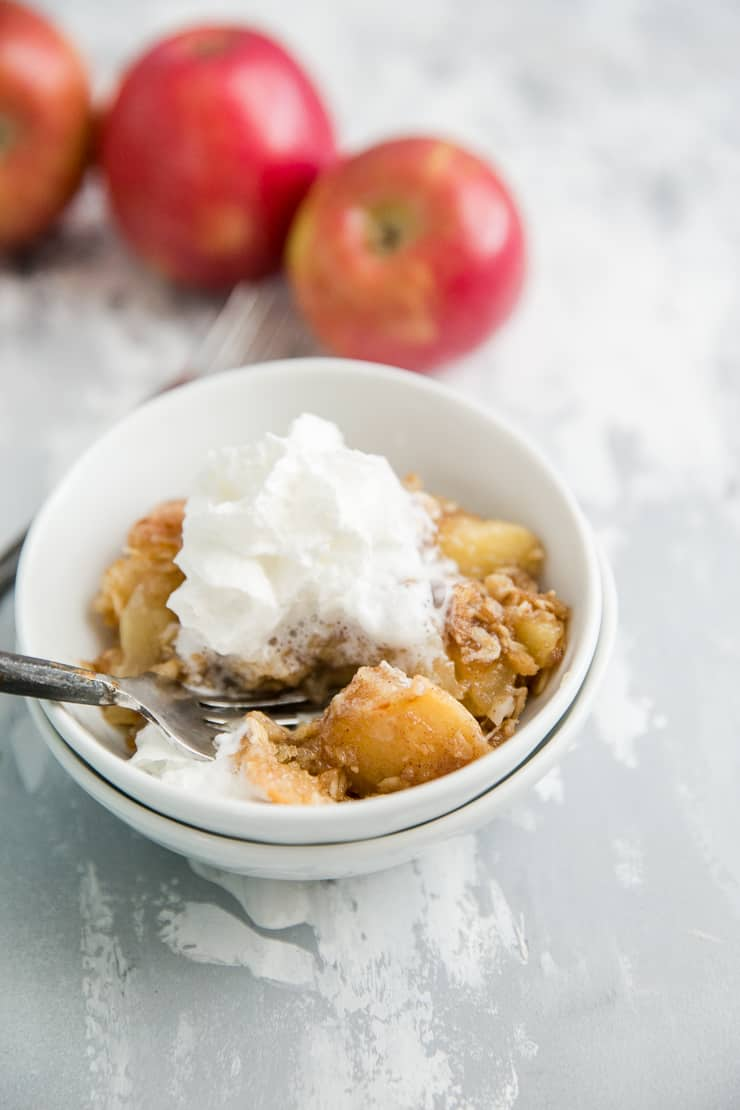 apple crisp in a bowl with whipped cream and a fork