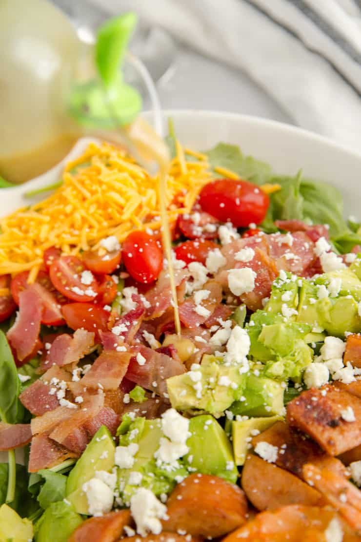dressing poured on the cobb salad