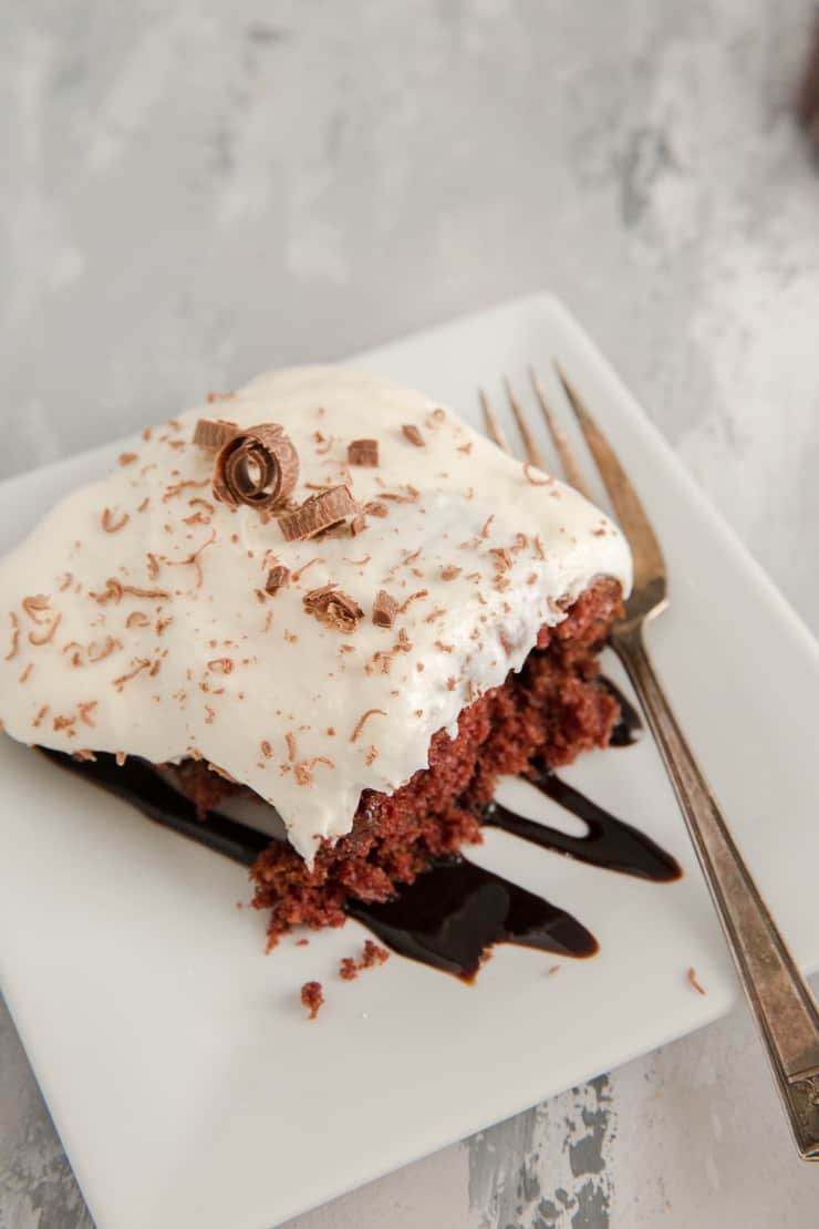 poke cake on a white plate with chocolate sauce